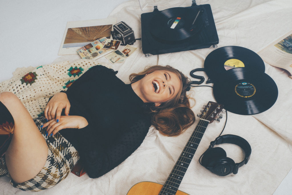Kerri Medders laughing in a 60's inspired photo shoot Vinyl Records vintage Polaroids Record player Martin acoustic guitar